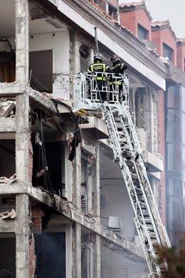 Dos bomberos trabajan en un inmueble momentos posteriores a una fuerte explosión registrada la calle Toledo