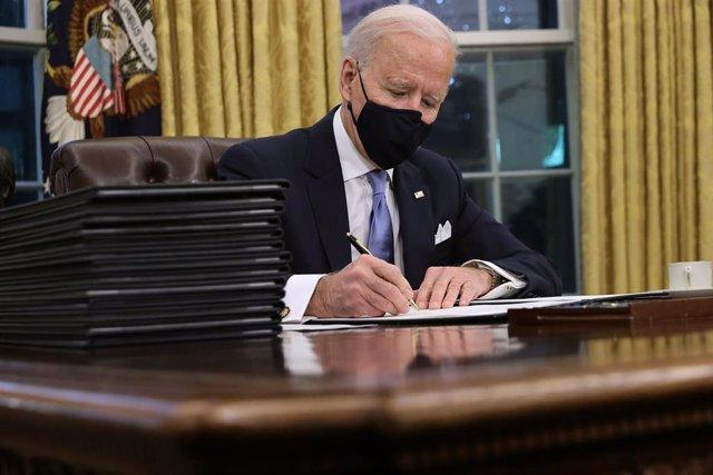 El presidente de Estados Unidos, Joe Biden, firma sus primeros decretos en el Despacho Oval.