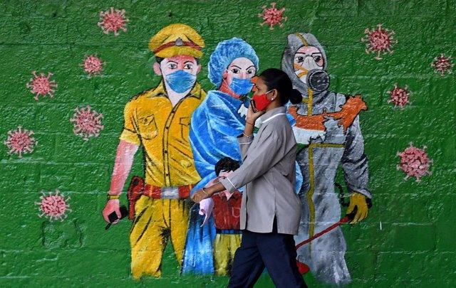 Una mujer con mascarilla frente a un mural en India durante la pandemia de coronavirus
