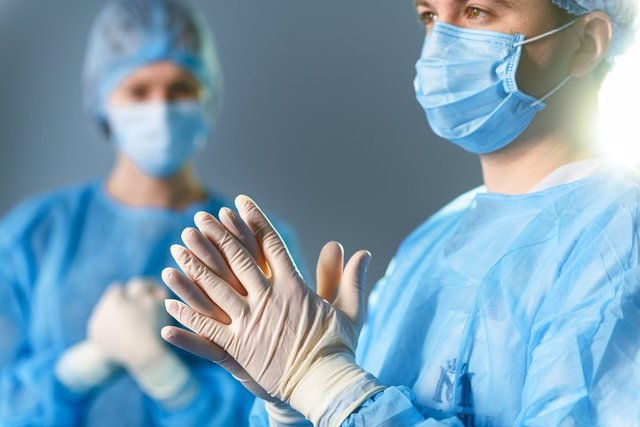 Concentrated doctors dressed in surgical uniform