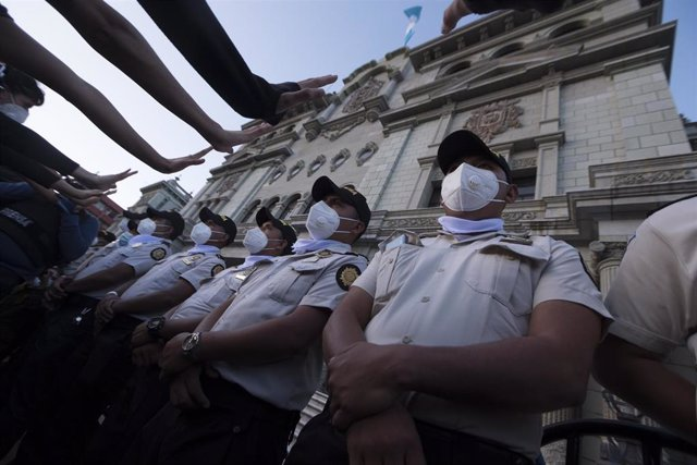 Agentes de la Policía de Guatemala con mascarilla frente al Palacio Nacional  en un día de protestas.