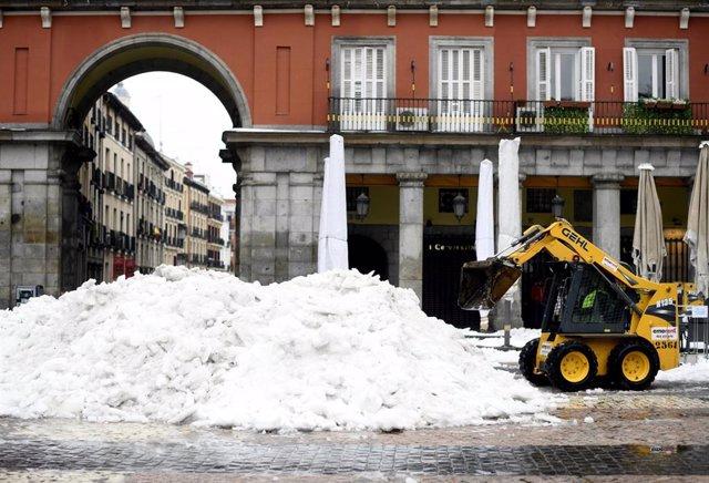 Una máquina excavadora continúa con las tareas de limpieza de calles tras la gran nevada provocada por la borrasca 'Filomena', en la Plaza Mayor, Madrid (España), a 20 de enero de 2021. 'Filomena' dejó paso ayer al temporal de lluvias 'Gaetán' que complic