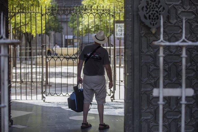 Un turista observa el Patio de los Naranjos desde la salida de la Catedral de Sevilla.