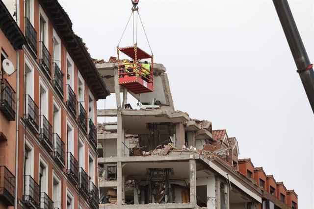 Varios operarios colgados de una grúa trabajan en la inspección ocular del edificio