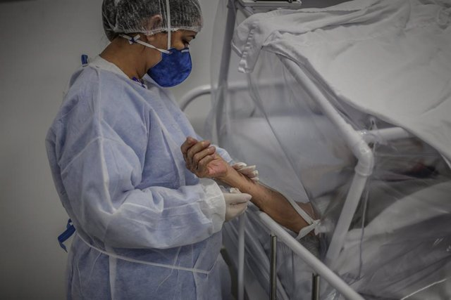 Una enfermera sujeta la mano de un paciente afectado por COVID-19 en Manaos.