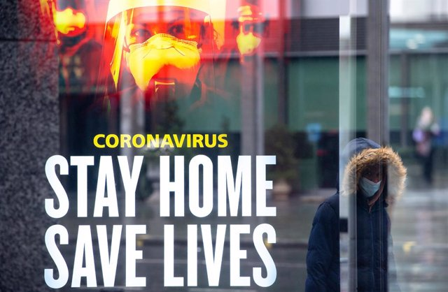 14 January 2021, England, London: A woman walks past a government conronavirus 'stay home, save lives' advert in central London during England's third national lockdown to curb the spread of coronavirus. Photo: Dominic Lipinski/PA Wire/dpa