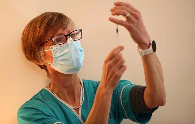 20 January 2021, United Kingdom, Shrewsbury: Dr Sarah Watton prepares the BioNTech/Pfizer Coronavirus (Covid-19) vaccine for elderly residents at Bowbrook House care home. Photo: Nick Potts/PA Wire/dpa