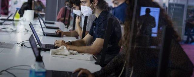 Joves treballant amb ordinadors portàtils durant la pandèmia de la Covid-19