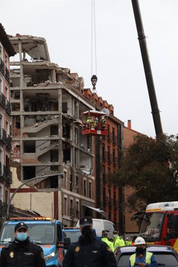 Varios operarios colgados de una grúa trabajan en la inspección ocular del edificio tras la explosión de ayer en la calle Toledo, en Madrid (España), a 21 de enero de 2021. La Policía Municipal de Madrid está retirando esta mañana los vehículos dañados po