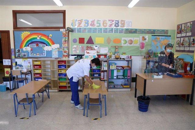 Una limpiadora desinfecta un aula ante el Covid-19