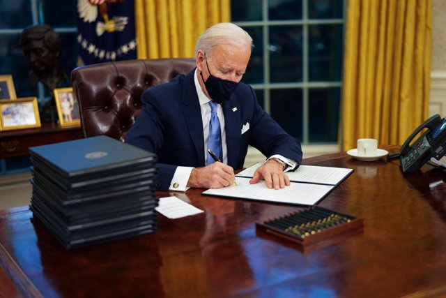 January 20, 2021 - Washington, DC, United States: United States President Joe Biden signs executive order on Covid-19 during his first minutes in the Oval Office, Wednesday, Jan. 20, 2021. President Biden as the 46th president of the United States. (Doug