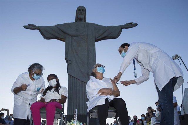 18 January 2021, Brazil, Rio de Janeiro: Two women receive coronavirus (Covid-19) vaccine during a vaccination campaign in front of the Christ the Redeemer statue. Photo: Fernando Souza/dpa