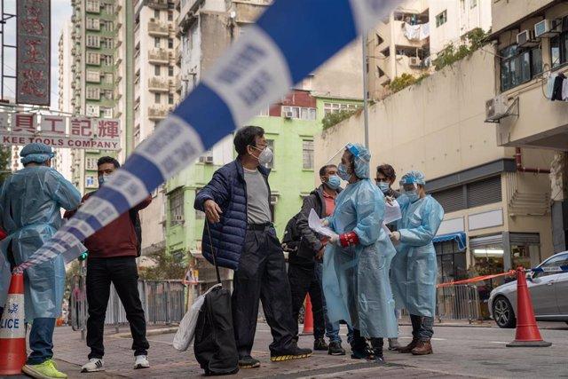 Un grupo de trabajadores sanitarios de Hong Kong ofrece información a un grupo de vecinos que acuden a hacerse la prueba obligatoria de coronavirus.