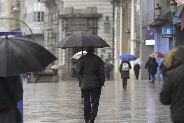 Transeúntes caminan protegidos por una vía de A Coruña