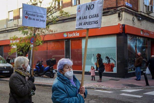 """Una mujer sostiene una pancarta donde se lee que """"Apostar la vida no es un juego"""" en una manifestación contra la proliferación de los locales de apuestas que ha tenido lugar en el barrio madrileño de Carabanchel, en Madrid (España), a 13 de diciembre."""