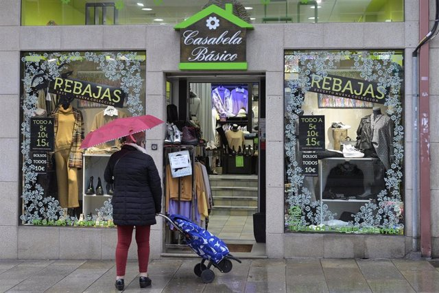 Una mujer en la puerta de un comercio en Arteixo, A Coruña
