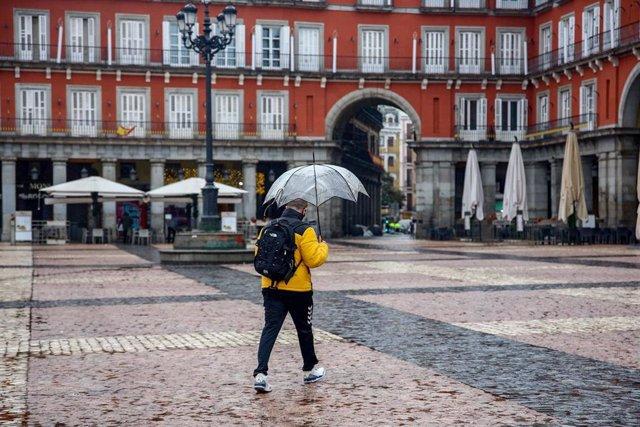 Un hombre camina protegido por un paraguas el mismo día de la llegada del temporal 'Gaetán', en la Plaza Mayor de Madrid, (España), a 20 de enero de 2021. El temporal de nieve y posterior frío provocado por la borrasca 'Filomena' terminó ayer para dejar a