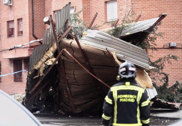 Bomberos del Ayuntamiento de Madrid trabajan en la retirada de la cubierta de un tejado arrancado por el viento en un edificio del distrito de Villa de Vallecas