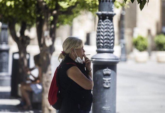Una persona fuma en la calle