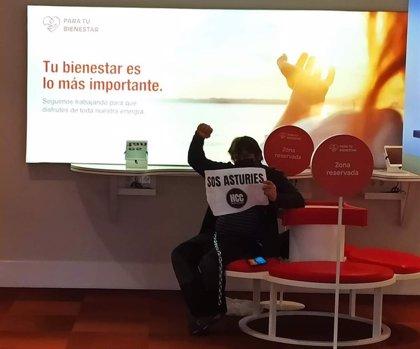 Un manifestante de Hostelería con Conciencia se encadena en la antigua oficina comercial de EDP en Gijón