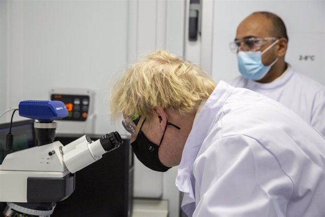 18 January 2021, United Kingdom, Oxford: UK Prime Minister Boris Johnson wearing a face mask looks at a microscope in the quality control laboratory, where batches of Coronavirus vaccine are tested, during a tour of the manufacturing facility for the Oxfo