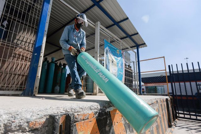 21 January 2021, Mexico, Queretaro: A worker carries an oxygen cylinder inside a factory while people line up to buy oxygen for their relatives infected with the coronavirus disease (COVID-19). Mexico faces a shortage of oxygen tanks and a fourfold rise i