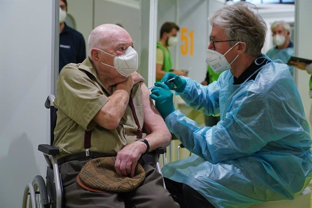 18 January 2021, Berlin: Herri Rehfeld (L), 92 years old, receives the coronavirus (Covid-19) vaccine at the vaccination centre on the Berlin exhibition grounds. Photo: Sean Gallup/Getty Images Europe/Pool/dpa