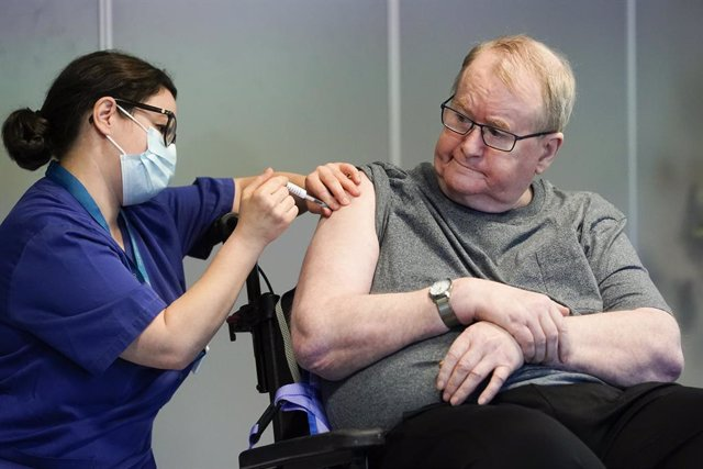 27 December 2020, Norway, Oslo: Nurse Maria Golding (l) vaccinates 67-year-old Svein Andersen with the Coronavirus vaccine from Biontech/Pfizer. Photo: Fredrik Hagen/NTB/dpa