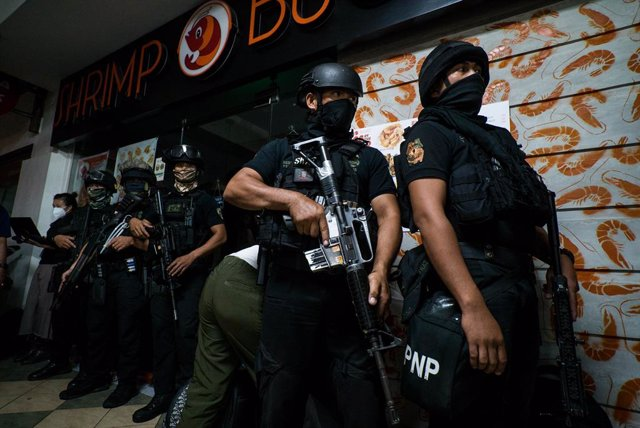 02 March 2020, Philippines, Manila: S.W.A.T. police officers hide behind a building as they prepare to tackle hostage taker Archie Paray. Police surrounded a shopping mall in the Greenhills district of Manila after Archie Paray, a recently dismissed secur