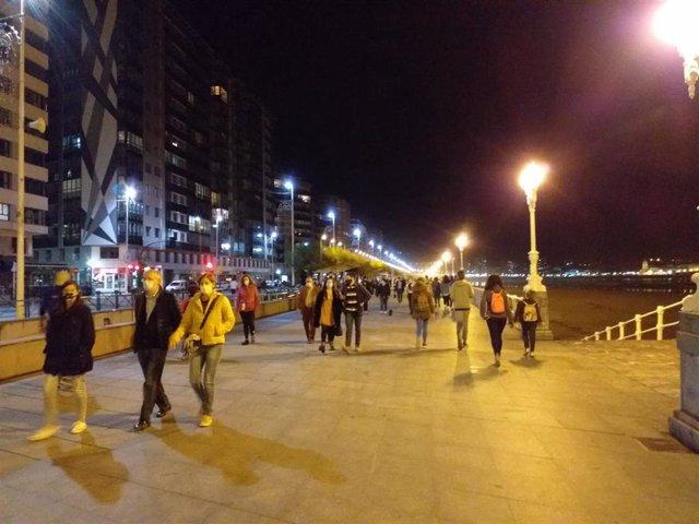 Vecinos de Gijón paseando por el Muro de San Lorenzo