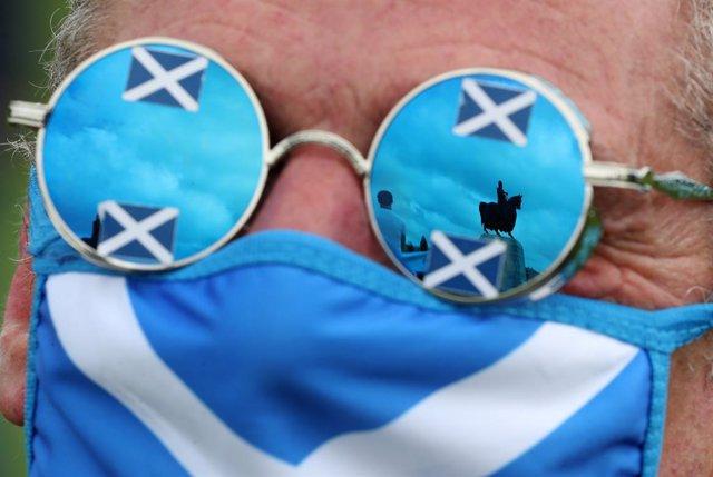 Un hombre con mascarilla y gafas de la bandera escocesa durante una manifesatción independentista en Bannockburn. En las gafas se ve reflejada una estatua ecuestre de Robert Bruce