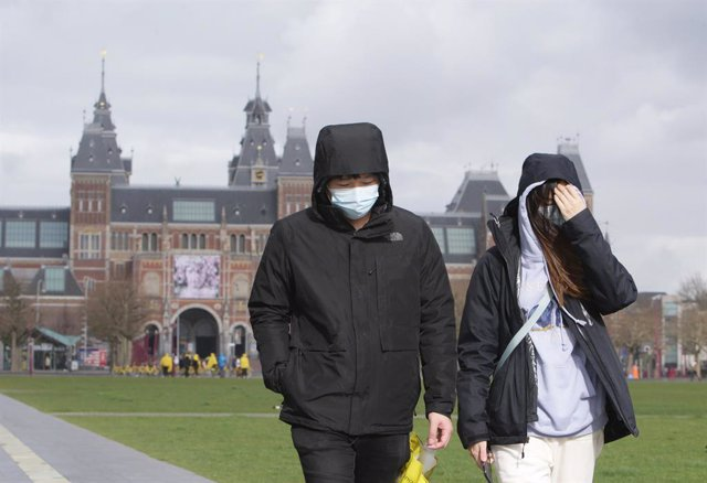 13 March 2020, Netherlands, Amsterdam: Two tourists wearing surgical masks, walk near the Rijksmuseum amid the coronavirus outbreak. Photo: Paulo Amorim/VW Pics via ZUMA Wire/dpa
