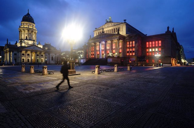 15 January 2021, Berlin: A passer-by walks across the otherwise deserted Gendarmenmarkt. The German Chancellor Angela Merkel and Minister Presidents of the federal states are to discuss further measures to contain the coronavirus pandemic on 19 January 20