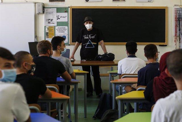 Un profesor y sus alumnos con mascarilla en una clase de un instituto en Roma