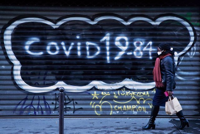 Una mujer con mascarilla frente a una persiana con una pintada de la COVID-19 en París, Francia