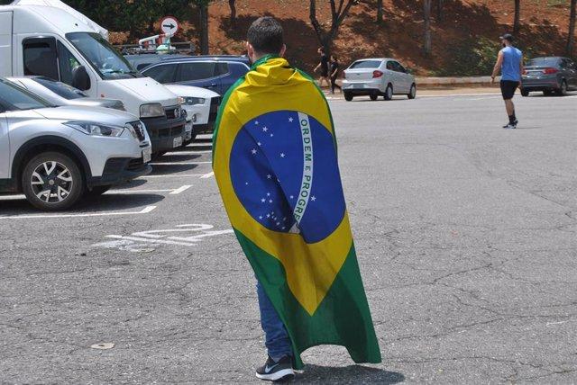 Un joven ataviado con la bandera de Brasil.