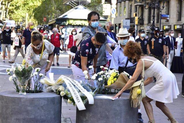 Asistentes dejan flores en recuerdo a las 16 personas fallecidas el 17 de agosto de 2017 y a los más de 150 heridos en los atentados de Barcelona y Cambrils durante el homenaje y minuto de silencio celebrado en Las Ramblas con motivo del tercer aniversari
