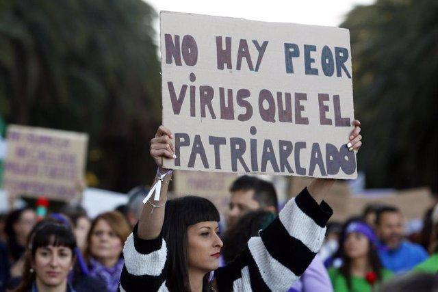 Una mujer sostiene una pancarta en la que se lee 'No hay peor virus que el patriarcado' durante la marcha por el Día Internacional de la Mujer en Málaga (Foto de archivo del 8 de marzo de 2020).