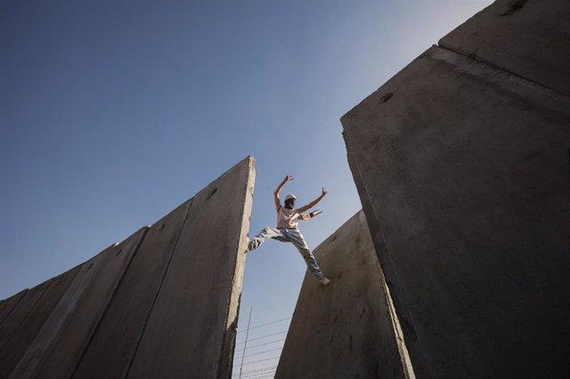 Palestino sobre una brecha del muro de Cisjordania en Ramala