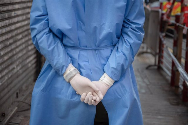 23 January 2021, China, Hong Kong: A health worker wearing latex gloves wait in an area where unprecedented lockdown has been declared by Hong Kong government in order to carry out compulsory coronavirus (COVID-19) testing in a designated zone.