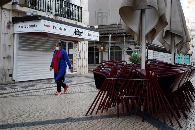15 January 2021, Portugal, Lisbon: A woman wears a face mask as she walks past by a closed restaurant on the first day of the second national lockdown to combat the COVID-19 Coronavirus pandemic. Photo: Pedro Fiuza/ZUMA Wire/dpa