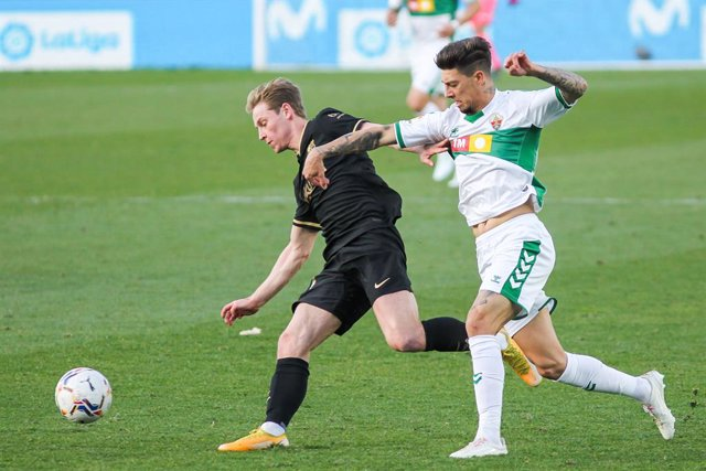 Frenkie de Jong of FC Barcelona and Emiliano Rigoni of Elche CF fight for the ball during La Liga football match played between Elche CF and FC Barcelona at Martinez Valero stadium on January 24, 2021 in Elche, Alicante, Spain.