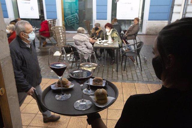 Una camarera se dispone a servir en una terraza de un restaurante de Avilés, Asturias (España), a 14 de diciembre de 2020.