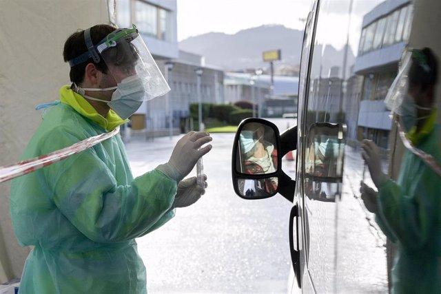 Una persona recoge su test de saliva desde el coche en la Avenida de Arsenio Iglesias en Arteixo, A Coruña, Galicia (España), a 24 de enero de 2021. El Servizo Galego de Saúde (Sergas) ha citado mediante un mensaje a los teléfonos a la población de entre
