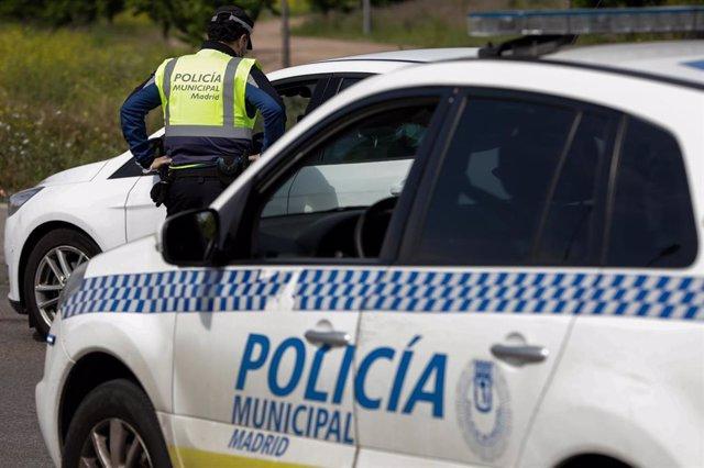 Un agente de la Policía Municipal pide a un conductor el justificante que le permite su salida de casa en un control policial de tráfico.