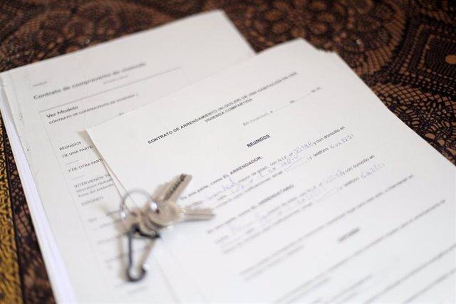 Unas llaves sobre un contrato de compraventa de vivienda y un contrato de arrendamiento (alquiler) de una habitación en una vivienda compartida.
