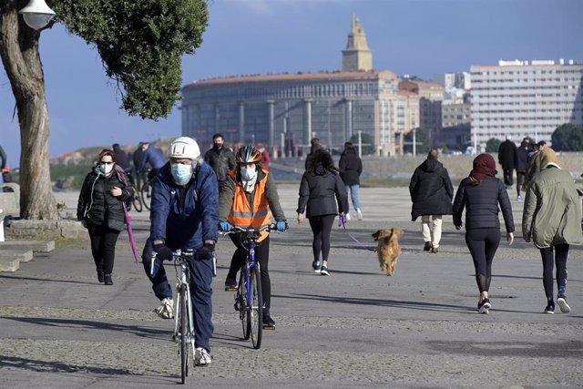 Varias personas caminan por un paseo marítimo en A Coruña, Galicia (España), a 10 de enero de 2021. En la jornada de este domingo, para la que se espera una ligera subida de las temperaturas, ya no habrá situación de alerta por frío en Galicia. Y es que,