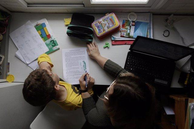 Un niño estudia y hace los deberes en casa con la ayuda de su madre