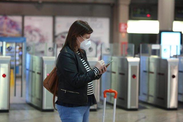 Una viajera con mascarilla consulta su móvil en la estación de Atocha, en Madrid (España), a 14 de mayo de 2020.