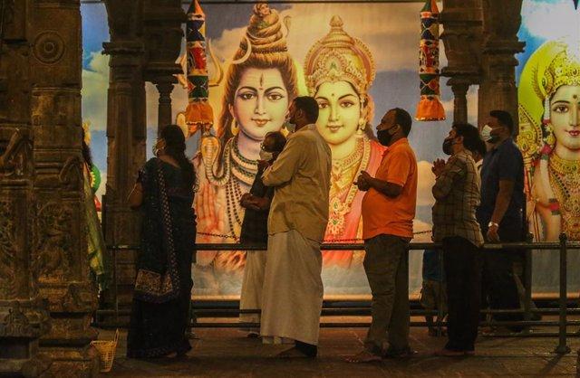 Personas con mascarilla por el coronavirus en un templo hindú de Sri Lanka